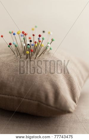 Pin cushion with multi-coloured pins in it
