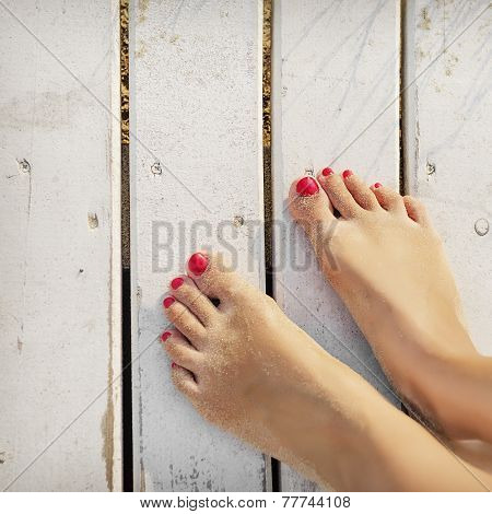 Women's Feet On The Boards Of The Pier