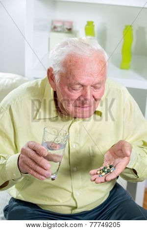 Elderly man drinking pills