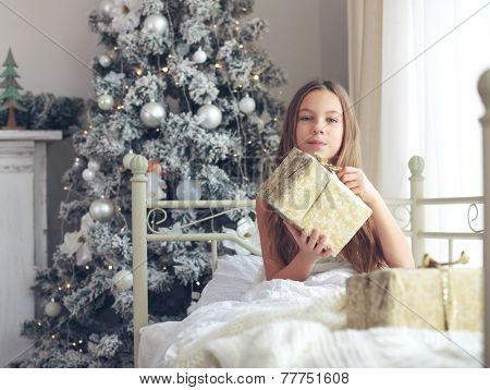 Preteen child girl wake up in her bed near decorated Christmas tree in beautiful hotel room in the holiday morning, enjoing with presents