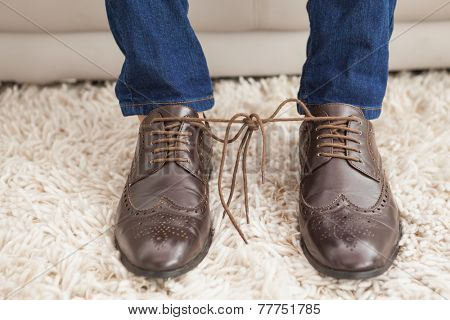 Classy mans shoelaces tied together at home in the living room