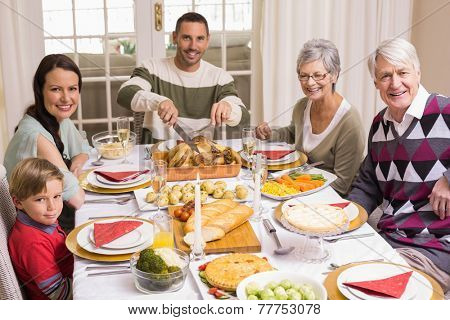 Man carving roast turkey during christmas dinner at home in the living room