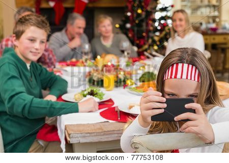 Little girl holding smartphone during christmas dinner at home in the living room