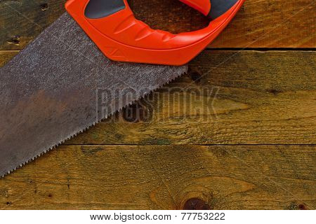 Red Woodsaw On Rustic Wooden Work Bench