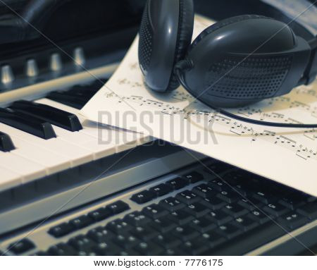Headphones and music sheet on keyboard