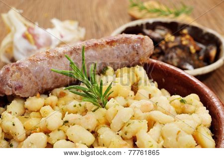 closeup of an earthenware bowl with botifarra amb mongetes, fried white beans and sausage typical of Catalonia, Spain