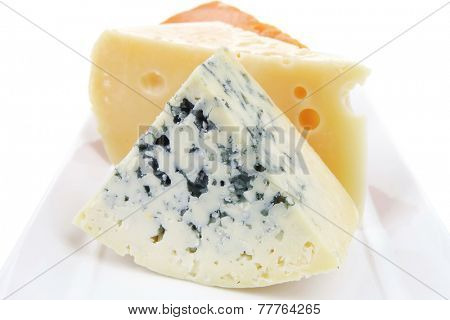 old blue stilton roquefort with orange cheddar and yellow parmesan on plate with isolated over white background