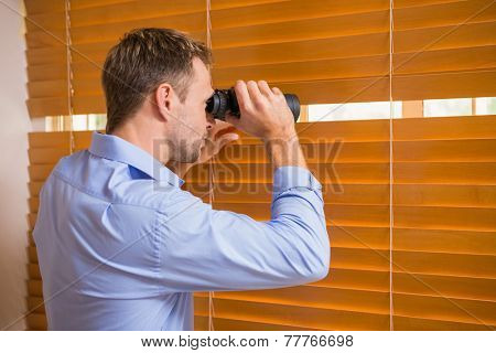 Man looking with binoculars through the blinds in the office