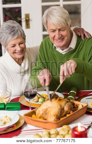 Man carving chicken while his wife having arm around him at home in the living room