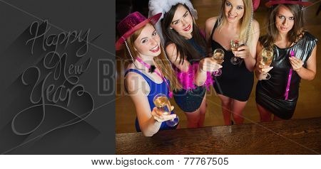 Happy gorgeous women holding flutes of champagne having hen party against classy new year greeting