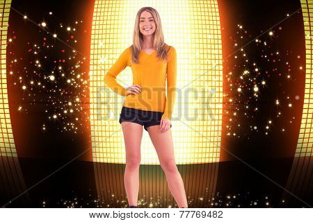 Stylish blonde smiling at camera against glittering screen on black background
