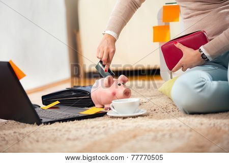 Young woman with laptop on the carpet trying to put credit cards in piggy bank