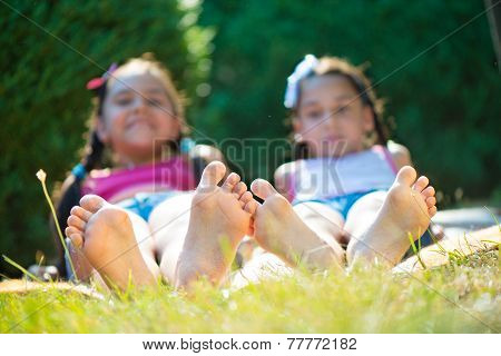 Two Happy Sisters Lying On Green Grass