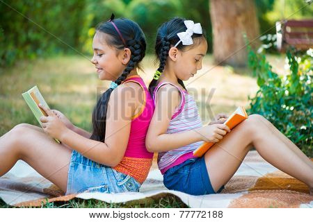 Sisters Reading Book In Summer Park