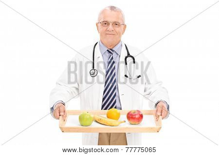 Mature doctor holding tray with a few fruits on it isolated on white background