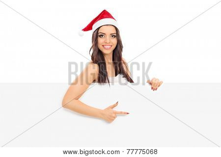 Female Santa pointing on a panel with her finger isolated on white background
