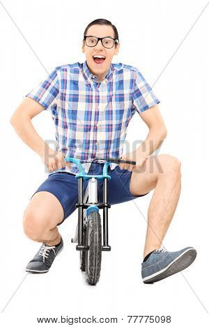 Silly young man riding a small childish bike isolated on white background