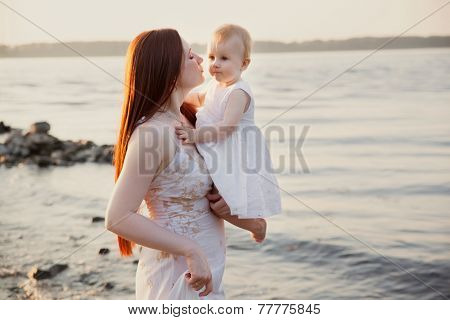 happy mother and daughter having fun at sunset beach