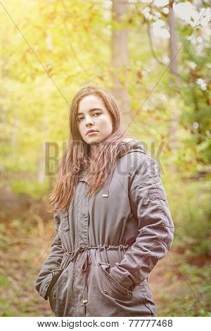 Portrait Of A Teenager Girl With Green Parka In An Autumn Forest