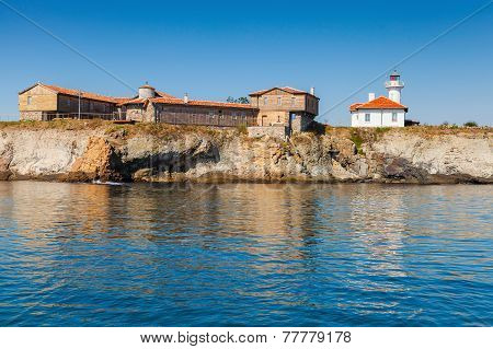 Lighthouse And Old Wooden Buildings On Island