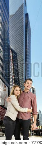 Young couple amidst tall skyscrapers in a big city, feeling totally in place and comfortable as city slickers