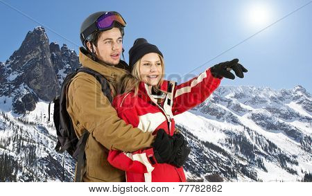 Sporty couple in front of a snowy mountain range in winter