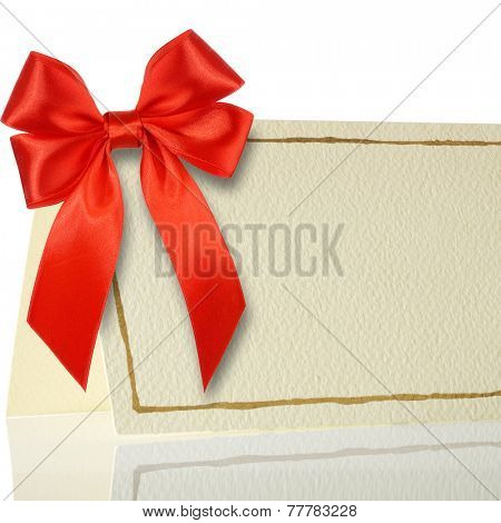 Blank gift tag tied with a bow of red satin ribbon. Isolated on white