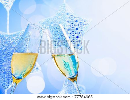Champagne Flutes With Golden Bubbles On Blue Christmas Lights Decoration Background