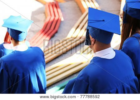 Graduate students wearing graduation hat and gown, outdoors