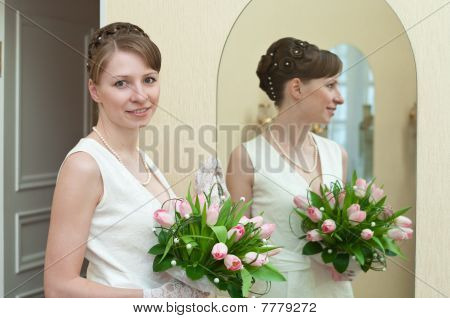 Young Woman A Bride Standing Near Mirror With Flowers In Hands. Reflection In Surface