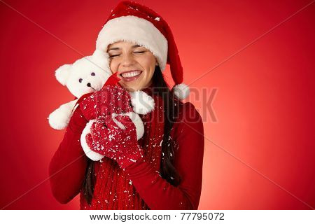 Glad girl in Santa cap embracing teddybear