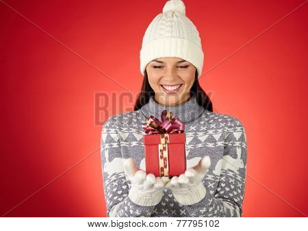 Portrait of smiling female looking at giftbox on her palms