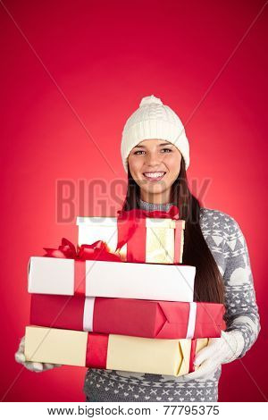 Portrait of happy girl in winterwear holding stack of giftboxes