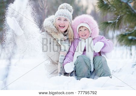 Happy parent and kid playing with snow in winter outdoor