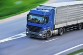 stock photo of moving van  - large van with load moves along road