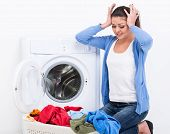 stock photo of dirty-laundry  - Tired housewife is doing laundry with washing machine at home - JPG
