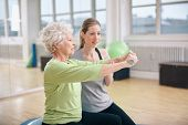 stock photo of geriatric  - Senior woman being assisted by instructor in lifting dumbbells at gym - JPG