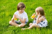 stock photo of little boys only  - Little girl and boy outdoor summer drink juice - JPG