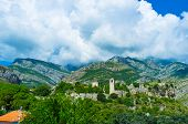 stock photo of greenery  - The ruins of the old fortress surrounded by greenery with the huge rocky mountains on the background Stari Bar Montenegro - JPG