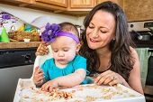 picture of messy  - Mother in messy kitchen smiles as baby eats - JPG
