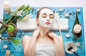 foto of face mask  - Young woman with spa facial mask on her face lying on blue table with flower - JPG