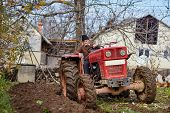 stock photo of plow  - Senior farmer on an old red tractor plowing his garden in the backyard  - JPG