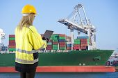 stock photo of container ship  - Female docker overlooking the unloading of a large container ship in an industrial harbor - JPG