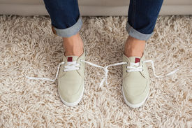 picture of prank  - Casual mans shoelaces tied together at home in the living room - JPG
