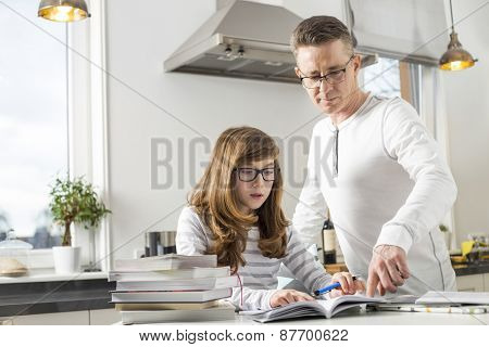 Father guiding daughter in doing homework at table