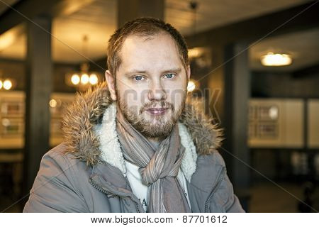 Russian man with beard sitting inside in a coat and scarf