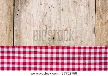 Red Checkered Tablecloth On A Rustic Wooden Background
