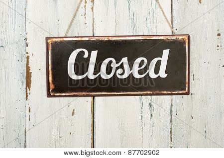 Old Metal Sign In Front Of A White Wooden Wall - Closed
