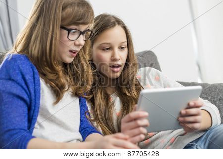 Shocked sisters using digital tablet on sofa at home
