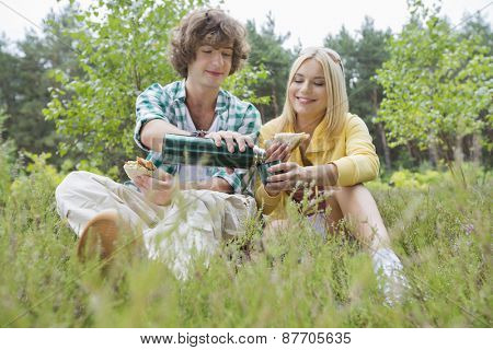 Young male hiker pouring coffee for woman while relaxing in field